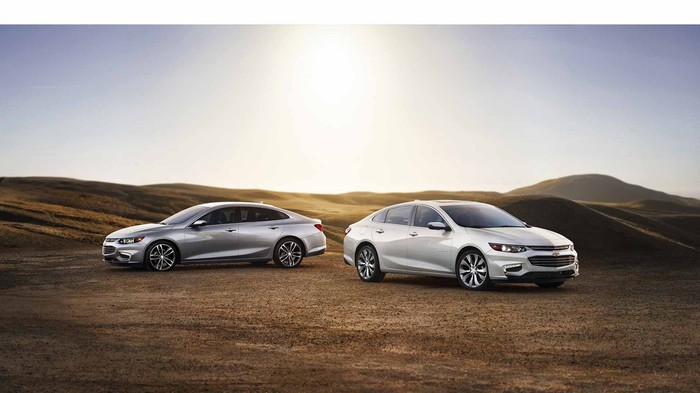 A white Chevy Malibu and a grey Chevy Malibu in a desert setting