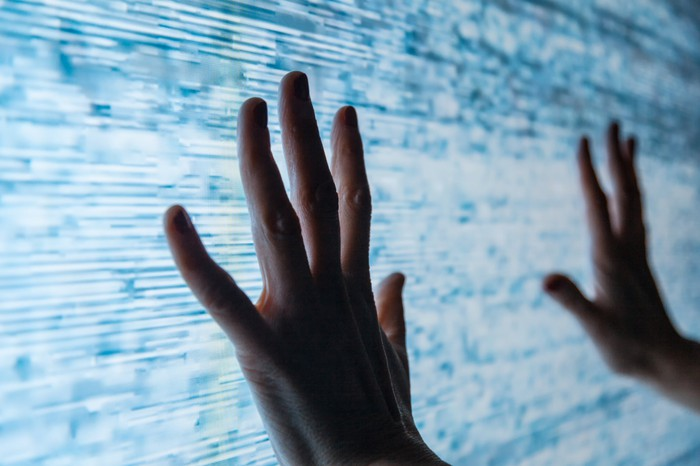 Two hands reach out to touch a large TV screen with a poor signal.