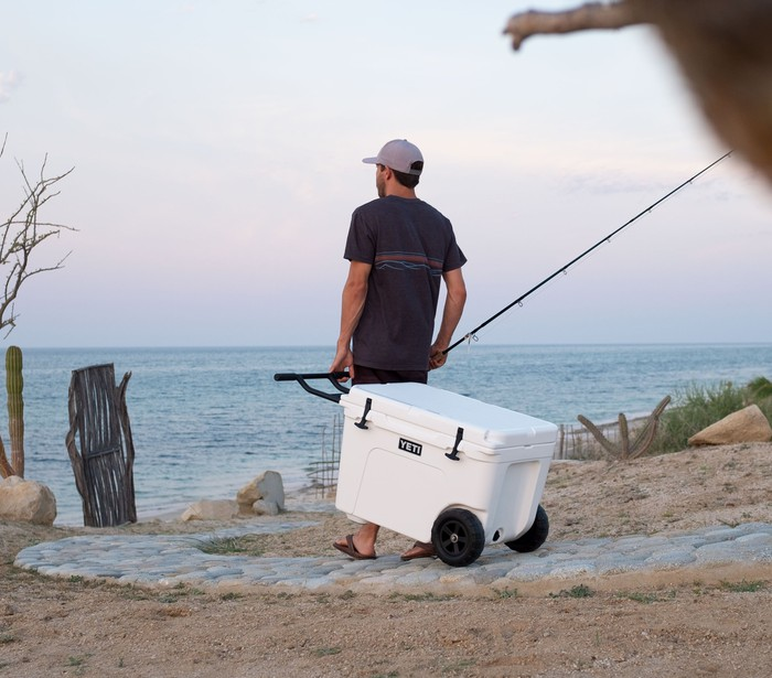 Man pulling Yeti cooler towards beach