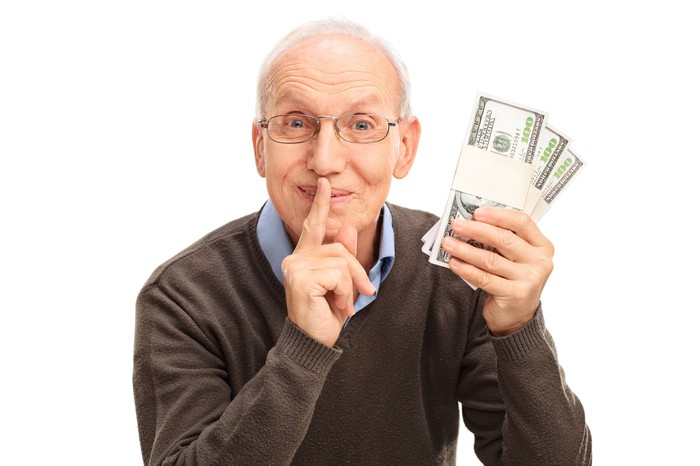 A senior man holds a finger to his lips while holding a stack of $100 bills in his other hand.