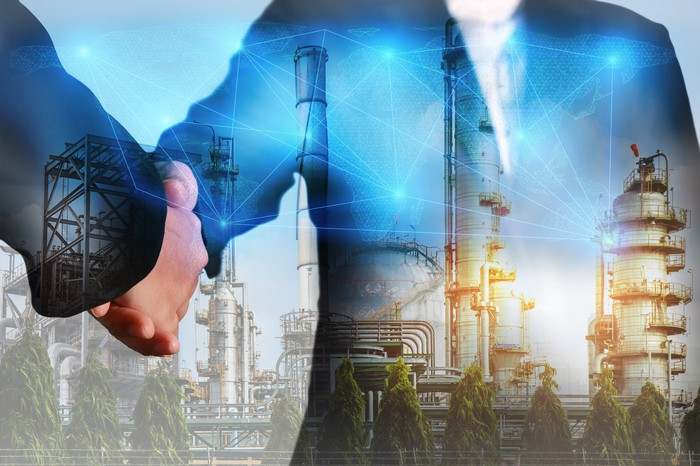 Two people shaking hands, with an energy facility in the background.