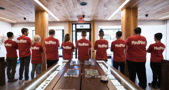 MedMen employees in store wearing red T-shirts with the company name on the back