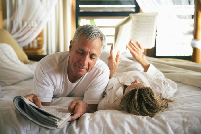 A senior couple reading in bed.