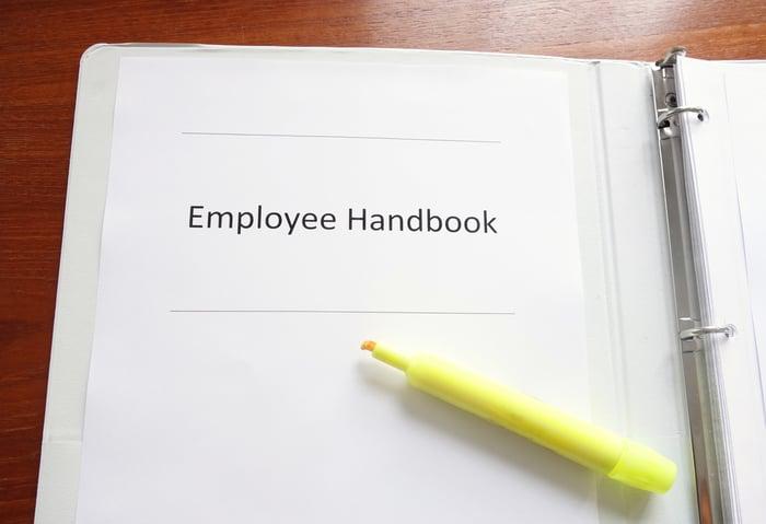 Yellow highlighter resting on employee handbook