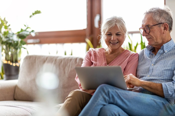 Adult couple smiling while looking at laptop at home.