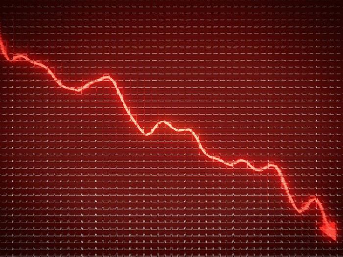 A jagged, lit-up arrow trending downwards in front of a red screen.