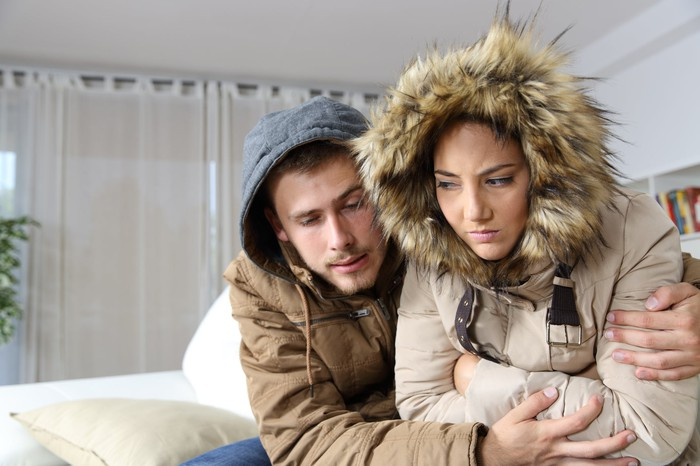 A young man and woman wearing coats indoors huddle together