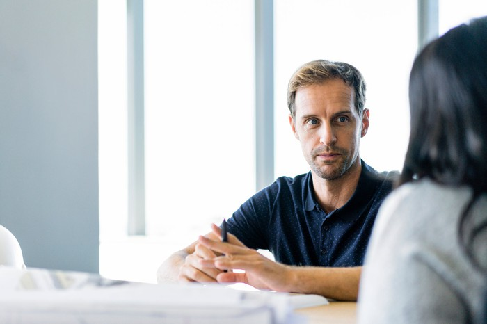 Man with a serious expression and a collared shirt sitting across from a woman in an office