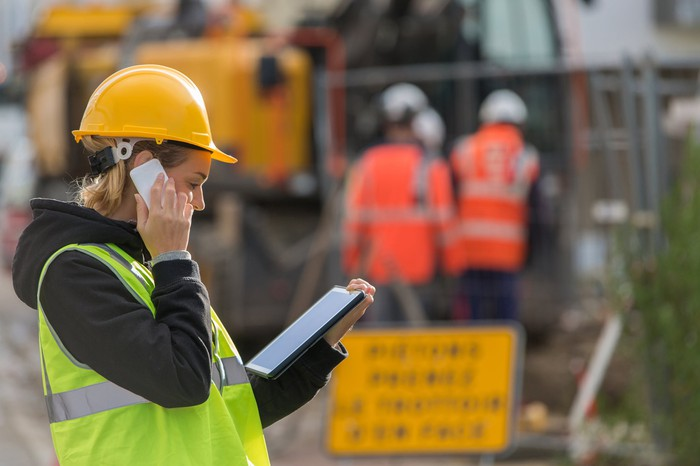 Female engineer using tablet device at construction site.