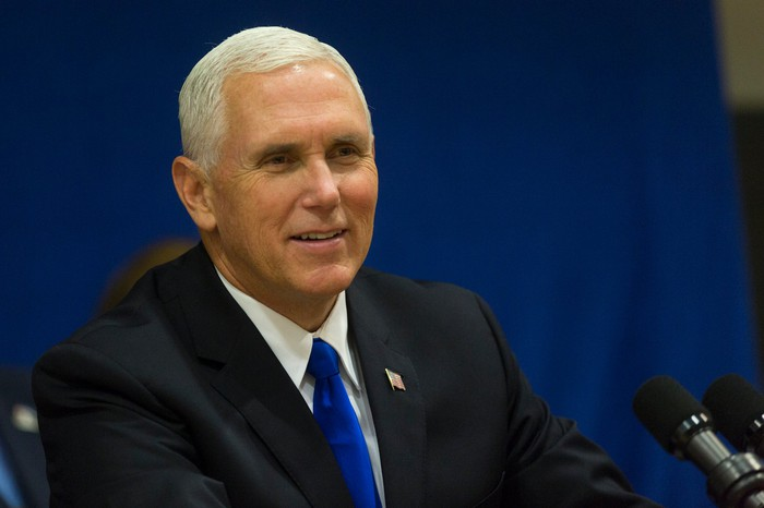 Vice President Mike Pence sitting behind a microphone and fielding questions.