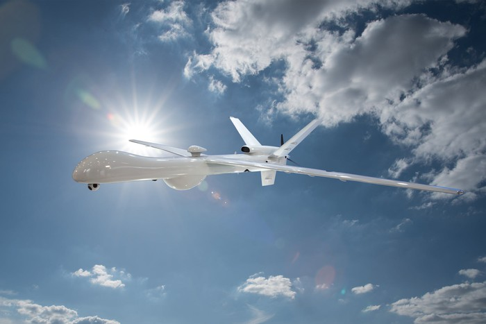 A military drone with a blue sky and bright sun behind it.