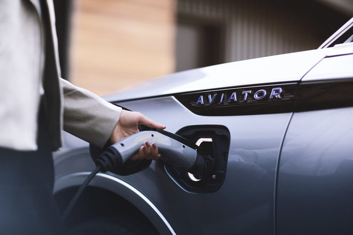 A close-up of the 2019 Lincoln Aviator Grand Touring's charging port. A man is shown holding a charging plug.