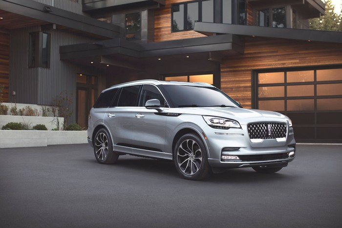 A silver 2019 Lincoln Aviator Grand Touring, parked in front of an upscale home. Surprisingly for a modern SUV, the softly-curved Aviator does not look large or imposing.