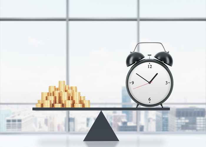 With a window in the background showing a city skyline, an alarm clock sits balanced on a board, with a stack of gold coins on the other end.