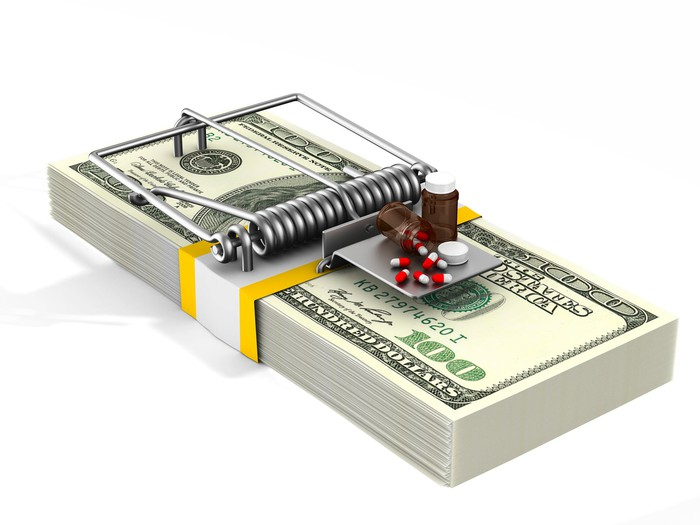 Medicine used as bait on a mouse trap made from a stack of cash.