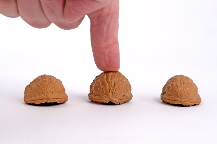 Finger on middle shell of three shells that are part of a shell game