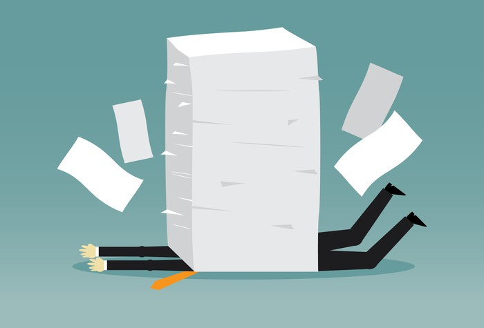 Cartoon of an office worker crushed by paperwork.