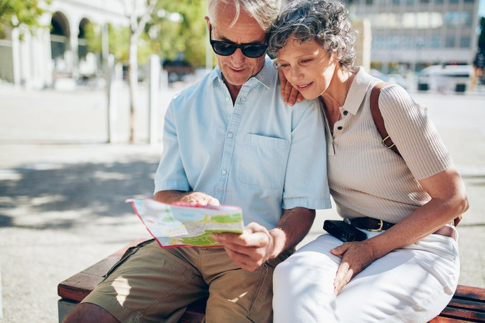 Mature couple sitting on a bench looking at a map.