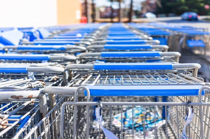 Many rows of blue shopping carts outside a store.