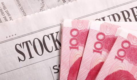 Chinese yuan notes on a newspaper stocks section