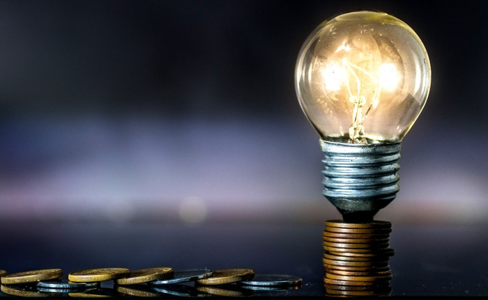 A light bulb sitting on a stack of coins with a trail of coins leading off to the left.