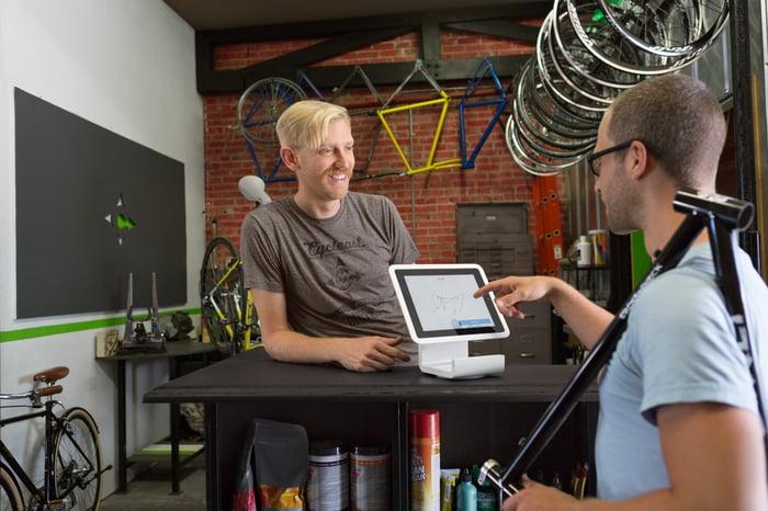 A merchant at a bike shop rings up a customer.
