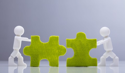Mini human figures pushing green jigsaw pieces