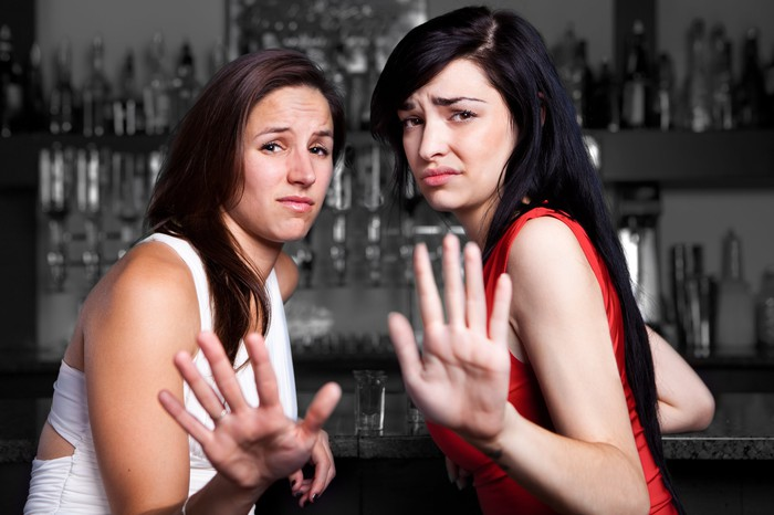 Two young women sit at a bar and hold up their hands, apparently saying no thanks.