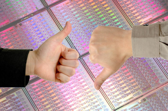 Two hands giving thumbs-up and thumbs-down signs in front of a large, uncut wafer of semiconductor silicon.