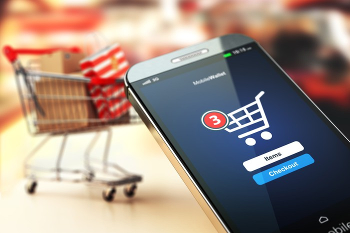 A smartphone showing an online shopping cart icon while a real shopping cart sits in a store aisle in the background.