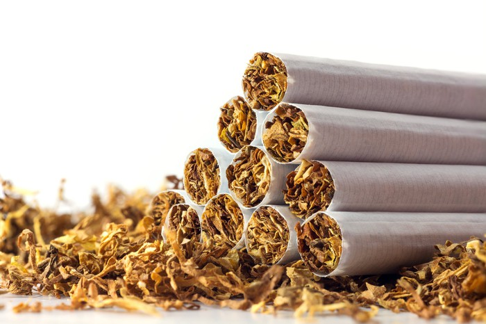 A pyramid of cigarettes stacked atop a bed of tobacco leaves.