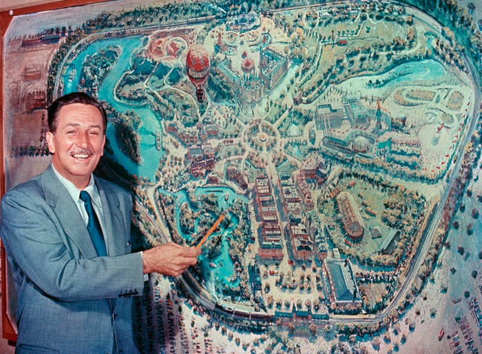 Walt Disney pointing to park plans.