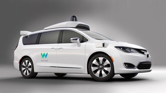 White minivan with self-driving technology on it and Waymo logo on the sliding door.