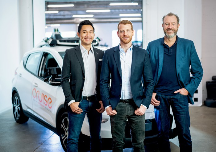Kan, Vogt, and Ammann are shown standing in front of a Cruise AV, a Chevrolet Bolt modified with self-driving hardware.