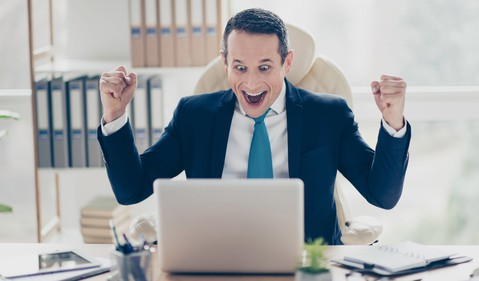 man at laptop smiling and excitedly raising arms_GettyImages-932294020