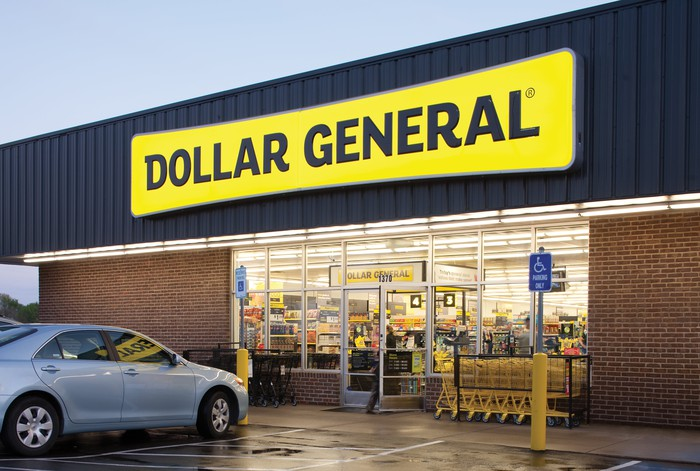 A Dollar General store with a silver car parked in front of it