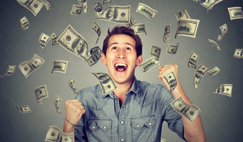 smiling young man surrounded by floating money_GettyImages-661886236