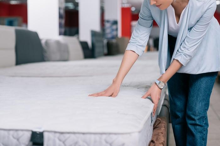 Woman shopping for a mattress.