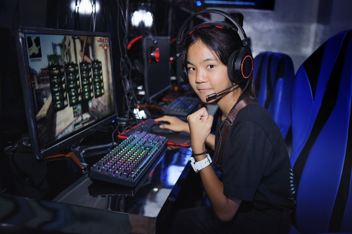 Girl gamer pumping fist playing PC game