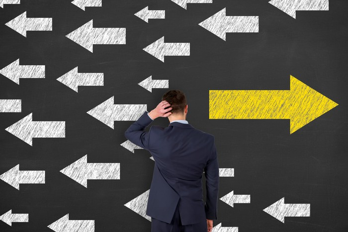 Man looking at a wall with several white arrows going one direction, one large yellow arrow pointing the opposite direction.
