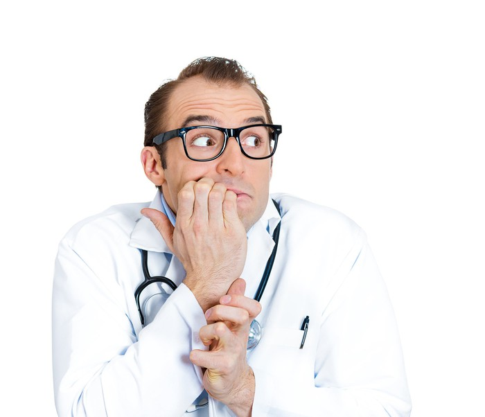 Doctor making a nervous expression that includes biting his nails.