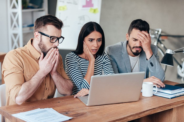 Three people looking at a computer screen and acting concerned.