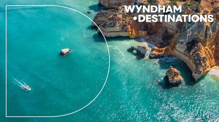 An aerial view of a boat in the water near cliffs along with the text Wyndham Destinations.