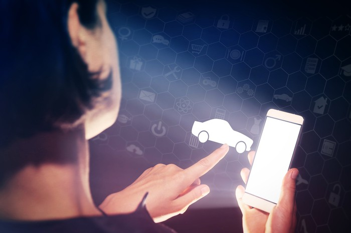 A woman holding a mobile phone and touching a car icon.
