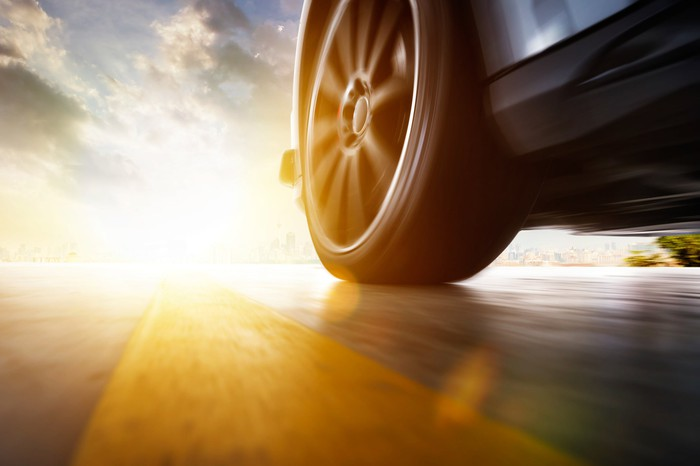 Close-up of a car's front left tire in motion next to a yellow line in the road