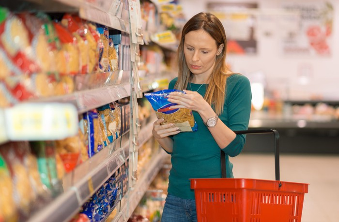 Woman holding a red basket and looking at a package of pasta at a dollar store.