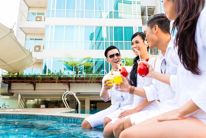 Two Chinese couples have drinks next to a pool.