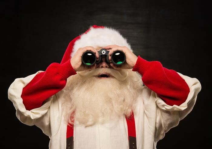 Santa Claus holding a pair of binoculars