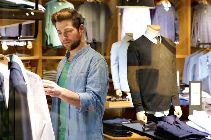 A man shopping for men's clothing in a department store.