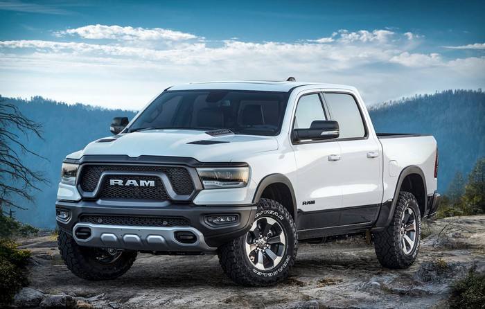 A white 2019 Ram 1500 Rebel, shown parked on a mountain road.